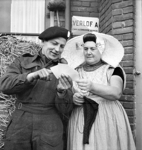A Canadian soldier shows a Dutch woman photos from home—evidence of the friendly relationship between Canadian soldiers, welcomed as liberators, and Dutch civilians. Photo credit: Bibliothèque et Archives Canada / PA-136320